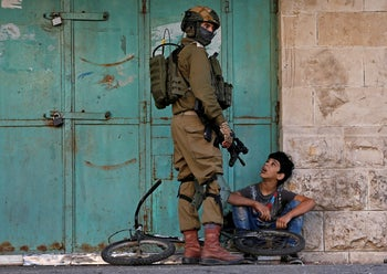 An Israeli soldier detains a Palestinian boy in Hebron, West Bank, November 29, 2019.