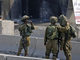 An Israeli soldier takes a picture of his comrades during a protest by Palestinians Qalandia checkpoint in the occupied West Bank, May 22, 2017.