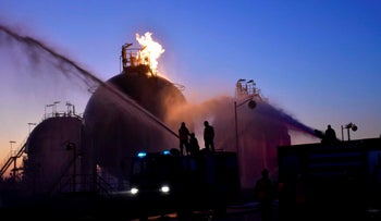 In this photo provided by Syria's state news agency, workers respond to an attack on Homs oil refinery on Dec. 21, 2019 in Homs, Syria.