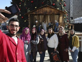 Palestinians pose for a selfie outside the Church of the Nativity, the site where Christians believe Jesus was born, in the West Bank biblical city of Bethlehem on December 19, 2019.