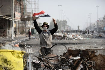 An Iraqi demonstrator carries the national flag in the Shiite holy city of Najaf on December 1, 2019.