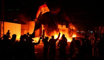 Iraqi demonstrators gather as flames start consuming Iran's consulate in the city of Najaf on November 27, 2019.
