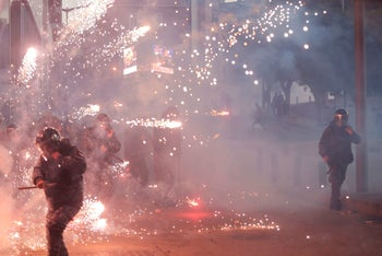 Lebanese riot police react to fireworks thrown by supporters of Hezbollah and Amal during clashes on December 14, 2019 in Beirut.