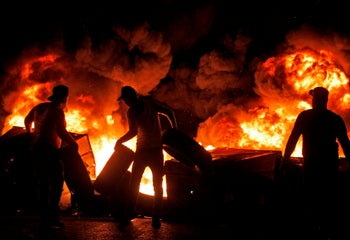 Protesters set aflame dumpsters and tires in the Lebanese city of Sidon on December 17, 2019.