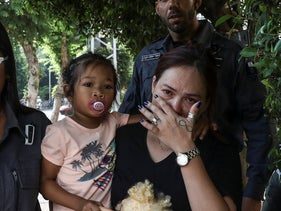 Geraldine Esta, a foreign worker, and her daughter being led out of her home by immigration authorities, July 23, 2019.