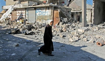 A Syrian woman walks past destruction at the site of a reported government bombardment in the village of Maasaran on the outskirts of Maaret al-Numan in the northwestern Idlib province, December 2019.