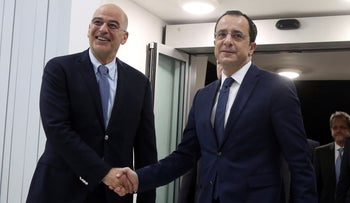 Greece's Foreign Minister Nikos Dendias, left, shake hands with Cypriot counterpart Nikos Christodoulides before their meeting in Larnaca, December 22, 2019.