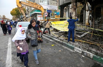 People walk near a burnt bank, after protests against increased fuel prices, in Tehran, Iran November 20, 2019.