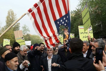 Iranian pro-government protesters burn an U.S. flag as they attend a demonstration in Tehran, Iran November 25, 2019.