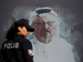 A Turkish police officer walks past a picture of slain Saudi journalist Jamal Khashoggi prior to a ceremony marking the one-year anniversary of his death, in Istanbul, October 2019.