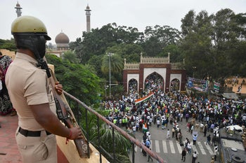 A security personnel stands guard as demonstrators arrive to take part in a rally against India's new citizenship law in Bangalore on December 23, 2019