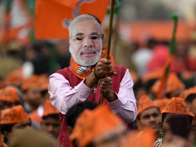A supporter of the Bharatiya Janata Party (BJP), wearing a mask with an image of India's Prime Minister Narendra Modi, waves a BJP flag during a rally in New Delhi on December 22, 2019
