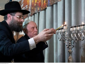 Holocaust survivor Mikhail Spectr, helped by Rabbi Aaron Mamut, lights a menorah during the annual Hanukkah Menorah Lighting Ceremony in Moscow, Russia, December 22, 2019.