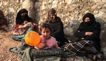 Displaced Syrians from the south of Idlib province sit out in the open in the countryside west of the town of Dana in the northwestern Syrian region on December 23, 2019.