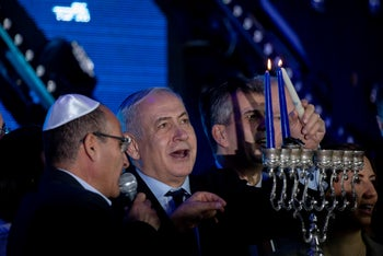 Netanyahu lighting Hanukkah candles during a Likud primary event in Jerusalem.