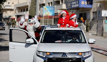 A family dressed as Santa Claus drive behind the convoy of Apostolic Administrator of the Latin Patriarchate of Jerusalem Pierbattista Pizzaballa in Bethlehem, December 24, 2019.