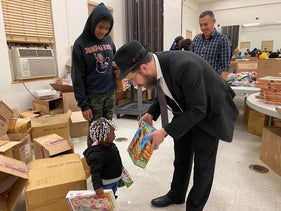 Rabbi Moshe Schapiro shows a toy to a child during the charity drive in Jersey City, New Jersey, December 23, 2019.