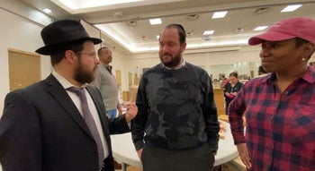 From left: Rabbi Moshe Schapiro, Chesky Deutsch and Pam Johnson talk during the charity drive in Jersey City, New Jersey, December 13, 2019.