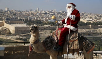 A man dressed in a Santa Claus costume rides a camel during the annual Christmas tree distribution organized by the Jerusalem municipality in Jerusalem's Old City, December 19, 2019.