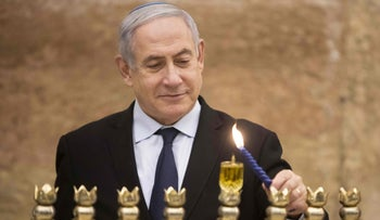 Israeli Prime Minister Benjamin Netanyahu lights a Hanukkah candle at the Western Wall in the Old City of Jerusalem, December 22, 2019