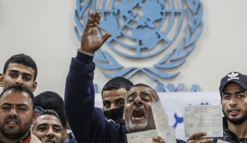 A man holding a refugee card shouts slogans as other demonstrators gather around him  during a protest calling on the United Nations Relief and Works Agency (UNRWA) to pay Palestinians for the repair of their homes, damaged during the 2014 Israel-Gaza conflict, at an UNRWA clinic in the village of Khuzaa on the eastern outskirts of the Palestinian city of Khan Yunis in the southern Gaza strip, on December 9, 2019.