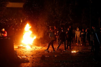 Demonstrators crowd around a stack of tires set on fire during a protest at the Corniche al Mazzraa in Beirut.