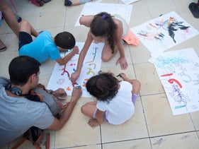 Children draw posters with Arabic writing on them as part of a mass protest in Tel Aviv against the the Nation-State law