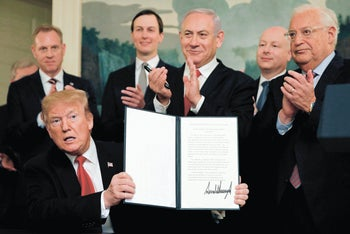 U.S. President Donald Trump holds a proclamation recognizing Israel's sovereignty over the Golan Heights as he is applauded by Prime Minister Benjamin Netanyahu and others during a ceremony at the White House in Washington, DC, March 25, 2019.