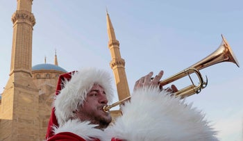 A Lebanese protester dressed in a Santa suit plays the trumpet in front of Mohammed al-Amin Mosque during ongoing anti-government protests in downtown Beirut, December 22, 2019