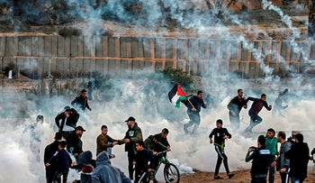 Palestinian protesters run from tear gas fired by Israeli forces amid clashes during a demonstration along the border with Israel east in the Gaza Strip on December 6, 2019.