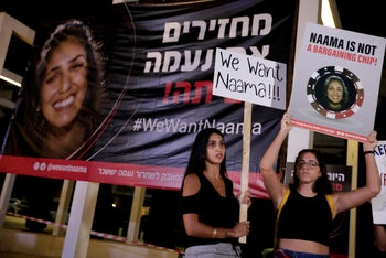 Israelis hold signs calling for the release of Naama Issachar during a demonstration In Tel Aviv, October 19, 2019.