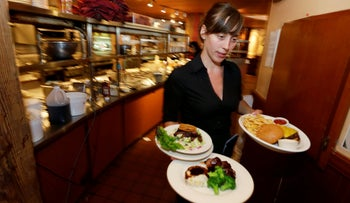 A waitress in Seattle carries food to a table as she works during lunchtime, 2014.