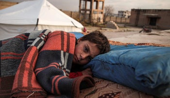 A Syrian child, one of those who fled from government forces' advance on Maaret al-Numan in the south of Idlib prvoince, sleeps on a futon in the open at a camp for the displaced near the town of Dana in the province's north near the border with Turkey, December 27, 2019