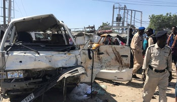 Somali security assess the scene of a car bomb explosion at a checkpoint in Mogadishu, Somalia  December 28, 2019.