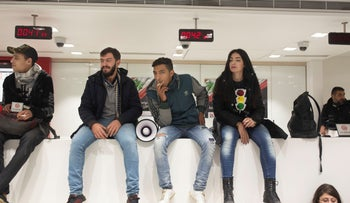 Anti-government protesters smoke cigarettes as they sit on the counter of the Hamra branch of BLC Bank, December 28, 2019.