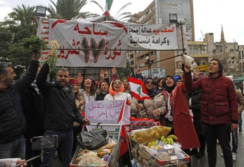 Protesters distribute food aid in Lebanon's southern city of Sidon on December 8, 2019.