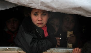 A Syrian child reacts upon her arrival in the back of a truck at a camp for displaced people in the Idlib province on December 27, 2019.