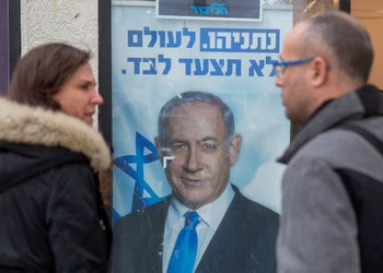 Israelis look at a poster of Netanyahu in Hadera, December 26, 2019.