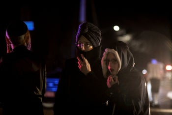 Onlookers standing near the scene of the stabbing during a Hanukkah celebration at a rabbi's home in Monsey, north of New York, December 29, 2019.