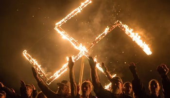 Supporters of the National Socialist Movement, a white nationalist political group, give Nazi salutes while taking part in a swastika burning at an undisclosed location in Georgia, U.S. on April 21, 2018