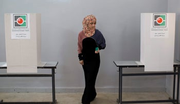 A Palestinian woman prepares to cast her vote at a polling station in the West Bank town of Kabatyeh, near Jenin, Saturday, Oct. 20, 2012
