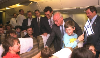 Prime Minister Yitzhak Rabin shaking hands with new Russian immigrants on their flight from Russia to Israel