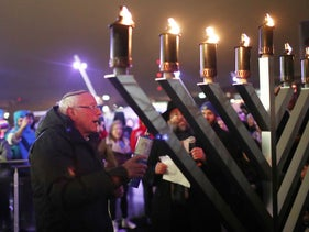 Senator Bernie Sanders (D-VT) uses a torch to light a menorah during a lighting event in Des Moines, Iowa, December 29, 2019.