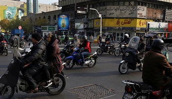 People ride motorcycles through an intersection in a commercial district of downtown Tehran, Iran, December 5, 2019.