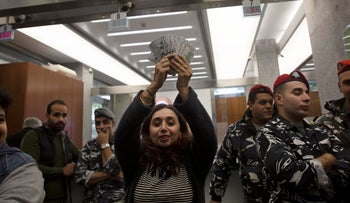 A woman holds up a stack of U.S. dollars she withdrew from a branch of Bank Audi in Beirut while it was occupied by anti-government protesters on December 30, 2019.