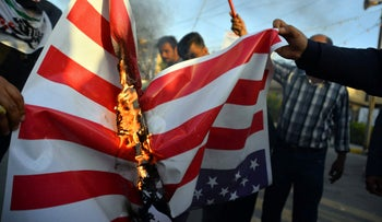Iraqis burn a U.S. flag during a demonstration to denounce the previous night's attacks by US planes on several bases belonging to the Hezbollah brigades, December 30, 2019.
