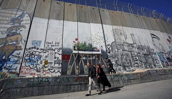 Palestinians walk along Israel's controversial barrier in the occupied West Bank town of Bethlehem on December 21, 2019.