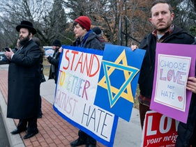 Neighbors gather carrying signs to show their support of the community near a rabbi's residence in Monsey, N.Y., Sunday, Dec. 29, 2019, following a stabbing Saturday night during a Hanukkah celebration.