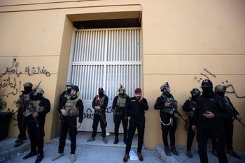 Members of Iraq's security forces stand guard outside one of the gates of the U.S. Embassy in Baghdad's Green Zone during an angry demonstration on December 31, 2019.
