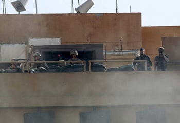 U.S. soldiers watch protests from behind a smoke screen at the U.S. embassy in Baghdad, Iraq, December 31, 2019.